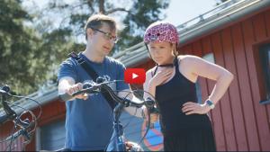 Linkki esittelyvideoon kesän 2018 kokeilukampanjasta, jossa oli mahdollista kulkea Korkeasaaren parkkipaikan ja portin välinen matka sähköpyörällä niin, että esimerkiksi perheen lapset matkustivat sähköpyörätaksin kyydissä aikuisten polkiessa. Kuvassa Ilmastoinfon työntekijä neuvoo kokeilijaa sähköpyörän hallintalaitteista.