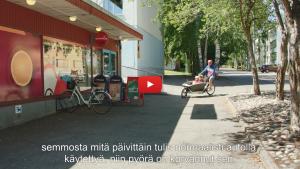 Linkki Virtaa fillariin -kokeilun 2018 minidokumenttiin, jossa kokeiluun osallistunut Mika kertoo kokeilun kulusta. Kuvassa Mika ajaa kaksi lasta perhepyörän kyydissä kaupan pihaan.