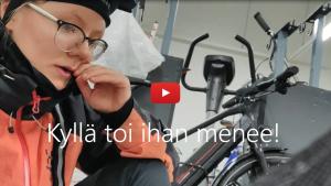 Linkki Virtaa fillariin -talvikokeilun 2020 somevideoon, jossa kokeiluun osallistunut Pipsa-Alisa kertoo fiiliksiä myrskyssä ajetun työmatkan jälkeen. Kuvassa Pipsa-Alisa pyöräkellarissa.