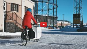 Linkki videoon, jolla tavarapyörien yhteiskäyttökokeilua markkinoitiin taloyhtiöille talvella 2019. Kuvassa nainen ajaa sähköavusteisella tavarapyörällä talvisessa Suvilahdessa.