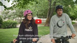 Linkki Virtaa fillariin -kokeilun 2018 minidokumenttiin, jossa kokeiluun osallistuneet Eevamaria ja Lauri kertovat kokeilun kulusta. Kuvassa Eevamaria ja Lauri ovat pysähtyneet pyörillään kommentoimaan ensivaikutelmia sähköpyöristä.