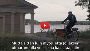 Linkki minidokumenttiin, jossa kerrotaan tavarapyörien yhteiskäyttökokeilusta vuokrakerrostaloissa kesällä 2019. Kuvassa kokeilutalon asukas ajaa sähköpyöröllä Stansvikin kartanon rannalla.